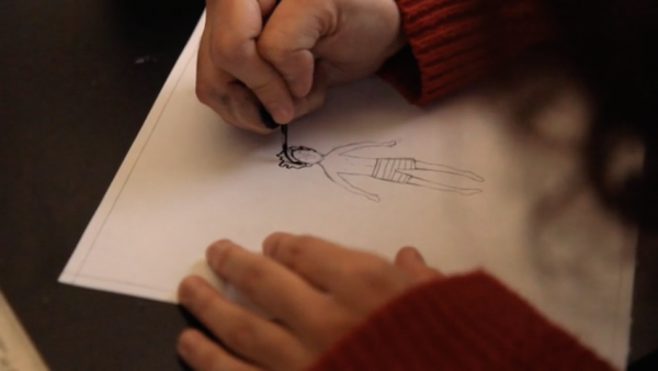 Leila drawing her father. He is always depicted in a black and white stripey shirt she copied from a photo she has of him. (Screenshot/Vimeo)