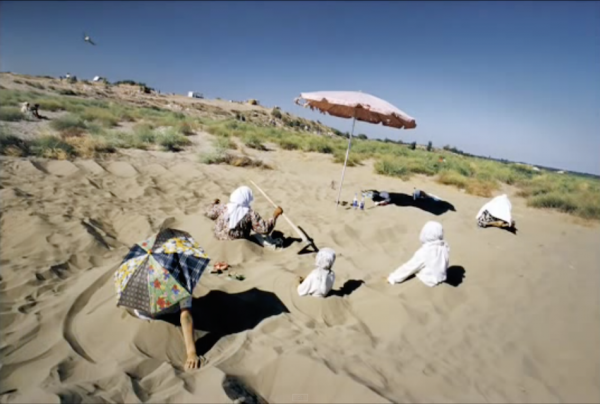UZBEKISTAN. Ferghana Valley. 2002. Muslim women digging themselves into what they believe to be healing sands.