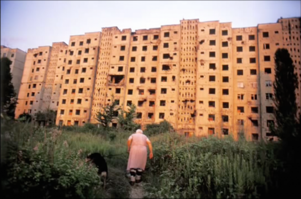 "GEORGIA. Abkhazia. Sukhum. 2005. Babushka ""Tanya,"" an elderly ethnic Russian woman, heads back to her bombed out apartment building after walking her dog. Despite the damages, three apartments remain occupied in the building. (Screenshot/YouTube)"