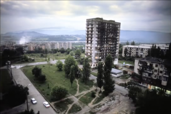 GEORGIA. Abkhazia. Sukhum. 2005. Damaged apartment building on the outskirts of Sukhum. Some of the apartments are still occupied. (Screenshot/YouTube)
