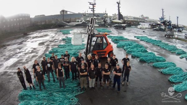 Sea Shepherd Conservation Society employees stand among the fishing nets collected on their 110-day expedition. The new shoe was made out of these nets. Image: Adidas