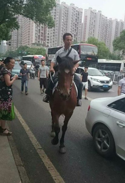 He attracts lots of attentions on his way to work. (Image: NTD TV)