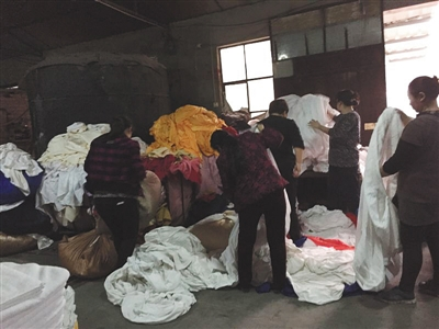 The workers were separating the linens in a workshop. (Image: Beijing News)