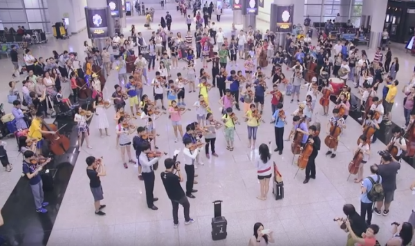 Music conductor and most of the orchestra members on the ground floor. (Screenshot via YouTube)