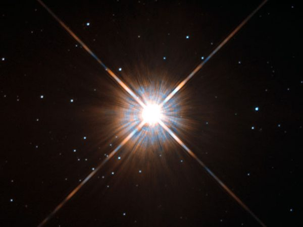 Shining brightly in this Hubble image is our closest stellar neighbour: Proxima Centauri. Proxima Centauri lies in the constellation of Centaurus (The Centaur), just over four light-years from Earth. Although it looks bright through the eye of Hubble, as you might expect from the nearest star to the Solar System, Proxima Centauri is not visible to the naked eye.