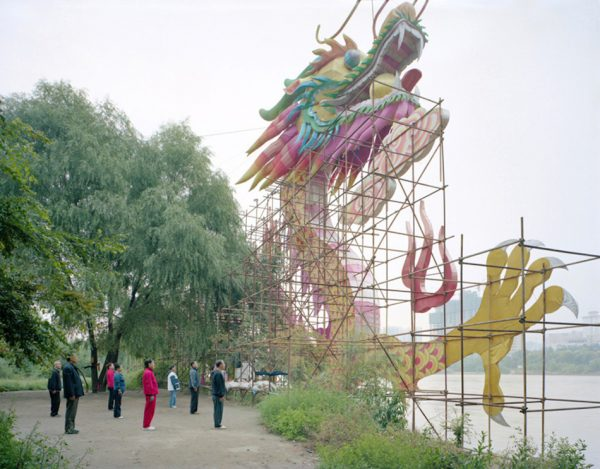 A group of people exercising under a dragon-like sign, Gansu province. (Image: Zhang Kechun)
