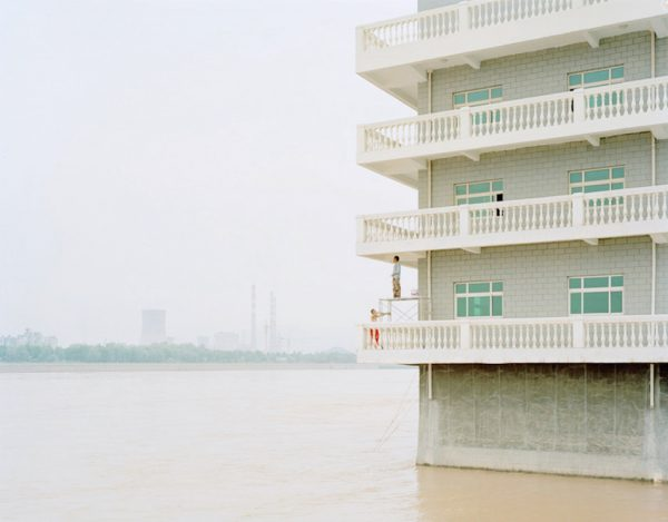 People Painting a House in the Middle of the River in Gansu, 2011. (Image: Zhang Kechun)