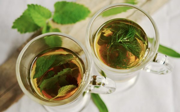 Place several fresh mint leaves into a cup and add hot water and sugar for taste. (Image: via pixabay / CC0 1.0)