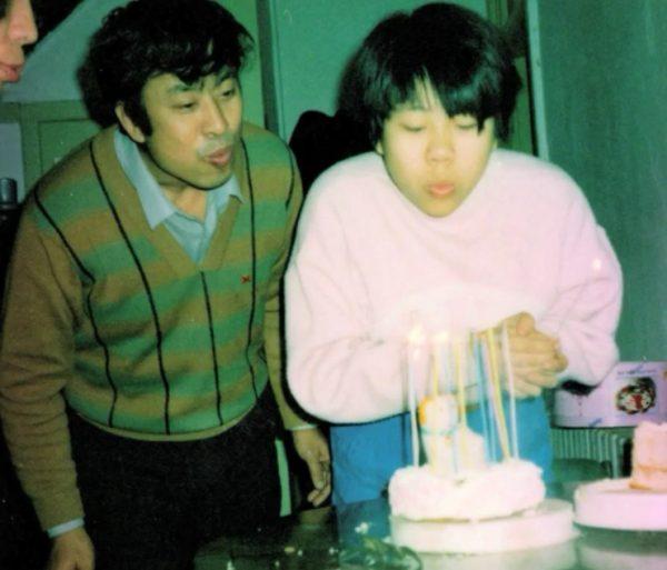 """Zhiwen Wang with his daughter, Xiaodan """"Danielle"""" celebrating one of her birthdays. (Image: FreeZhiwenWang via YouTube/Screenshot)"""