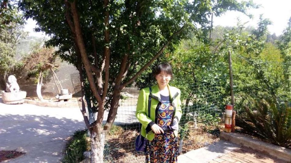 Iris's mother - Deng Cuiping, during spring time, in a local orchard of Yuxi city. (Image: Family Photo)