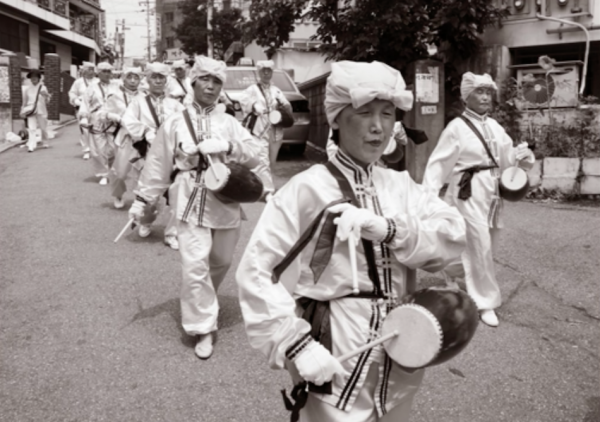 Korean Falun Gong practitioners do waist drum performances in a parade - the practitioners in Korea put in a lot of effort for the release of Chengnu. (Image via Jarrod Hall Vimeo/Screenshot)
