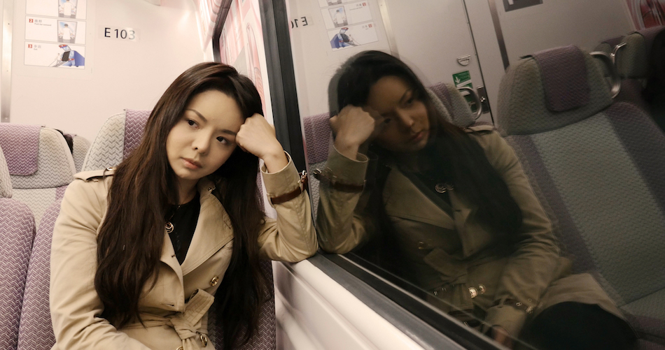 A thoughtful Anastasia Lin on a train often faced with the dilemma of having to choose between speaking out and staying silent.(Image via media kit Badass Beauty Queen Film)