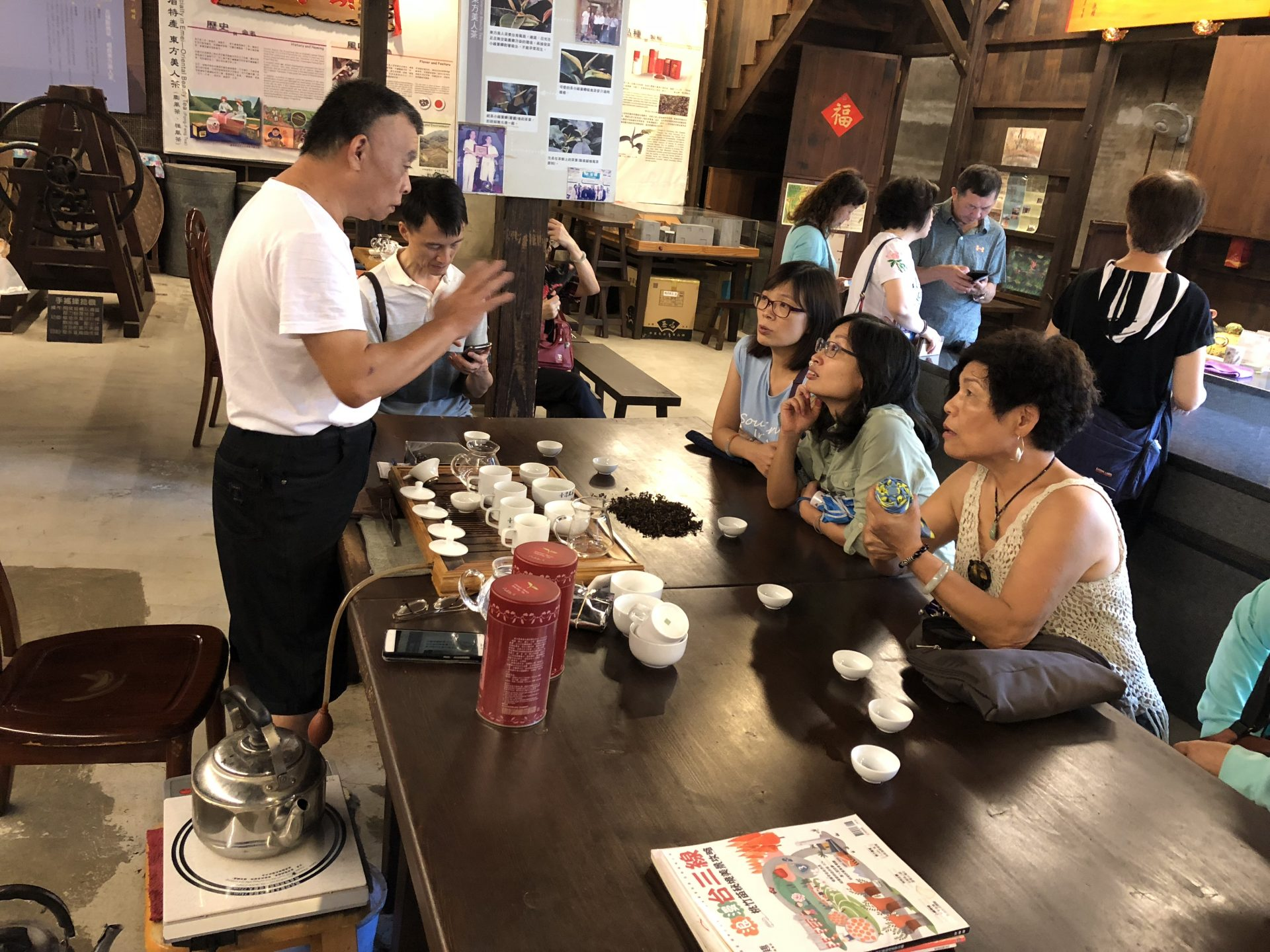 The operator of a hundred-year-old tea shop explain the history of the Oriental Beauty Tea to visitors (Image: Billy Shyu/ Vision Times)