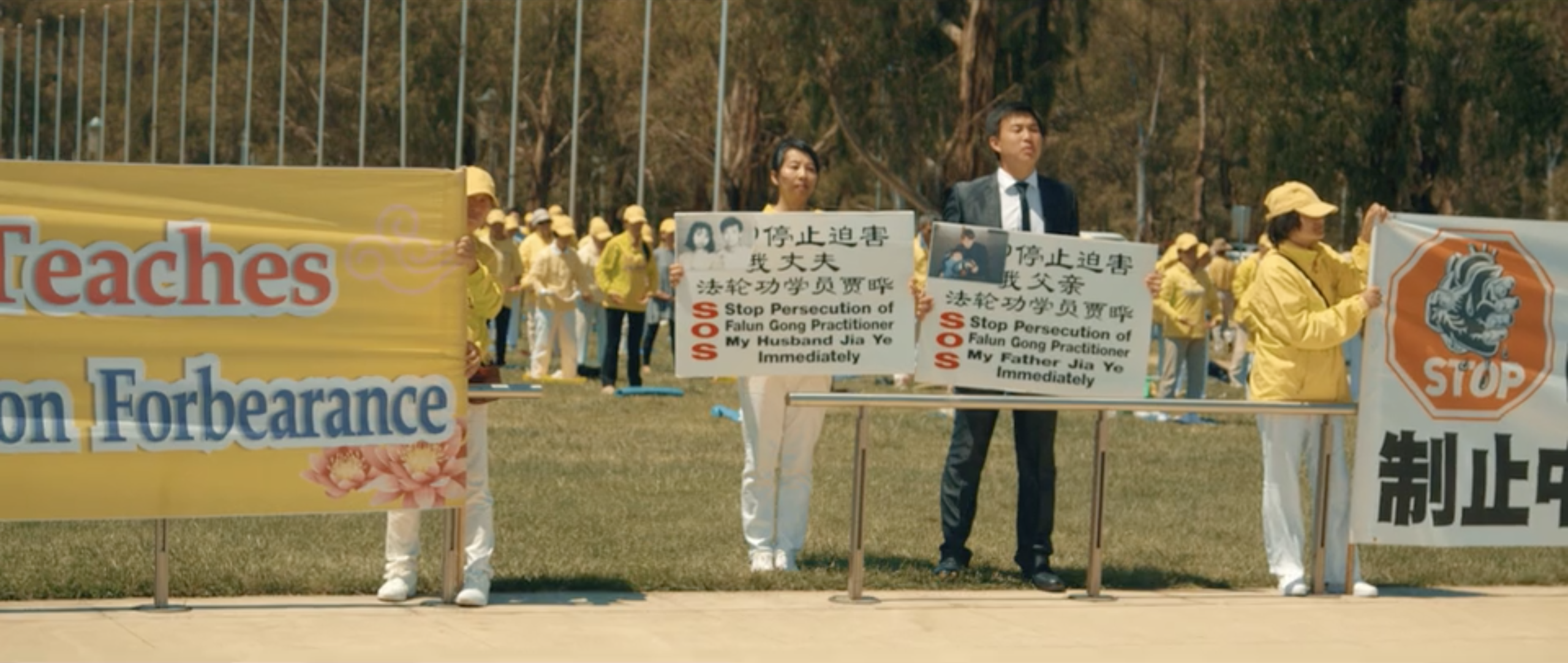 Eric and his mother peacefully protesting with other Falun Dafa practitioners who wish to see an end to the persecution of Falun Dafa in China, signs are held outside Parliament house in Canberra. (Image via Alexander Vimeo/Screenshot)