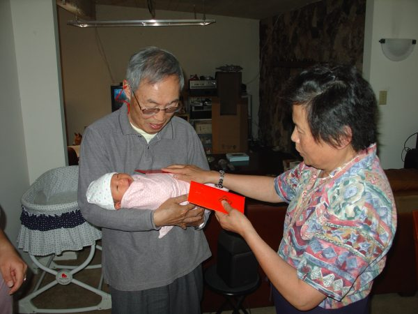 A red envelope is handed over at the birth of a child. (Image Credit: mliu92; Flickr; CC2.0)