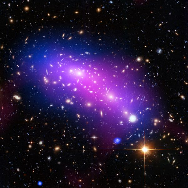 At first glance, this cosmic kaleidoscope of purple, blue and pink offers a strikingly beautiful — and serene — snapshot of the cosmos. This new image of the cluster combines data from three different telescopes: the NASA/ESA Hubble Space Telescope (showing the galaxies and stars), the NASA Chandra X-ray Observatory (diffuse emission in blue), and the NRAO Jansky Very Large Array (diffuse emission in pink). Each telescope shows a different element of the cluster, allowing astronomers to study MACS J0416 in detail. As with all galaxy clusters, MACS J0416 contains a significant amount of dark matter, which leaves a detectable imprint in visible light by distorting the images of background galaxies. In this image, this dark matter appears to align well with the blue-hued hot gas, suggesting that the two clusters have not yet collided; if the clusters had already smashed into one another, the dark matter and gas would have separated. MACS J0416 also contains other features — such as a compact core of hot gas — that would likely have been disrupted had a collision already occurred. Together with five other galaxy clusters, MACS J0416 is playing a leading role in the Hubble Frontier Fields programme, for which this data was obtained. Owing to its huge mass, the cluster is in fact bending the light of background objects, acting as a magnifying lens. Astronomers can use this phenomenon to find galaxies that existed only hundreds of million years after the big bang. For more information on both Frontier Fields and the phenomenon of gravitational lensing, see Hubblecast 90: The final frontier. Links Hubblecast 90: The final frontier Link to Hubblesite release (Image Credit: ESA/Hubble [CC BY 4.0], via Wikimedia Commons)