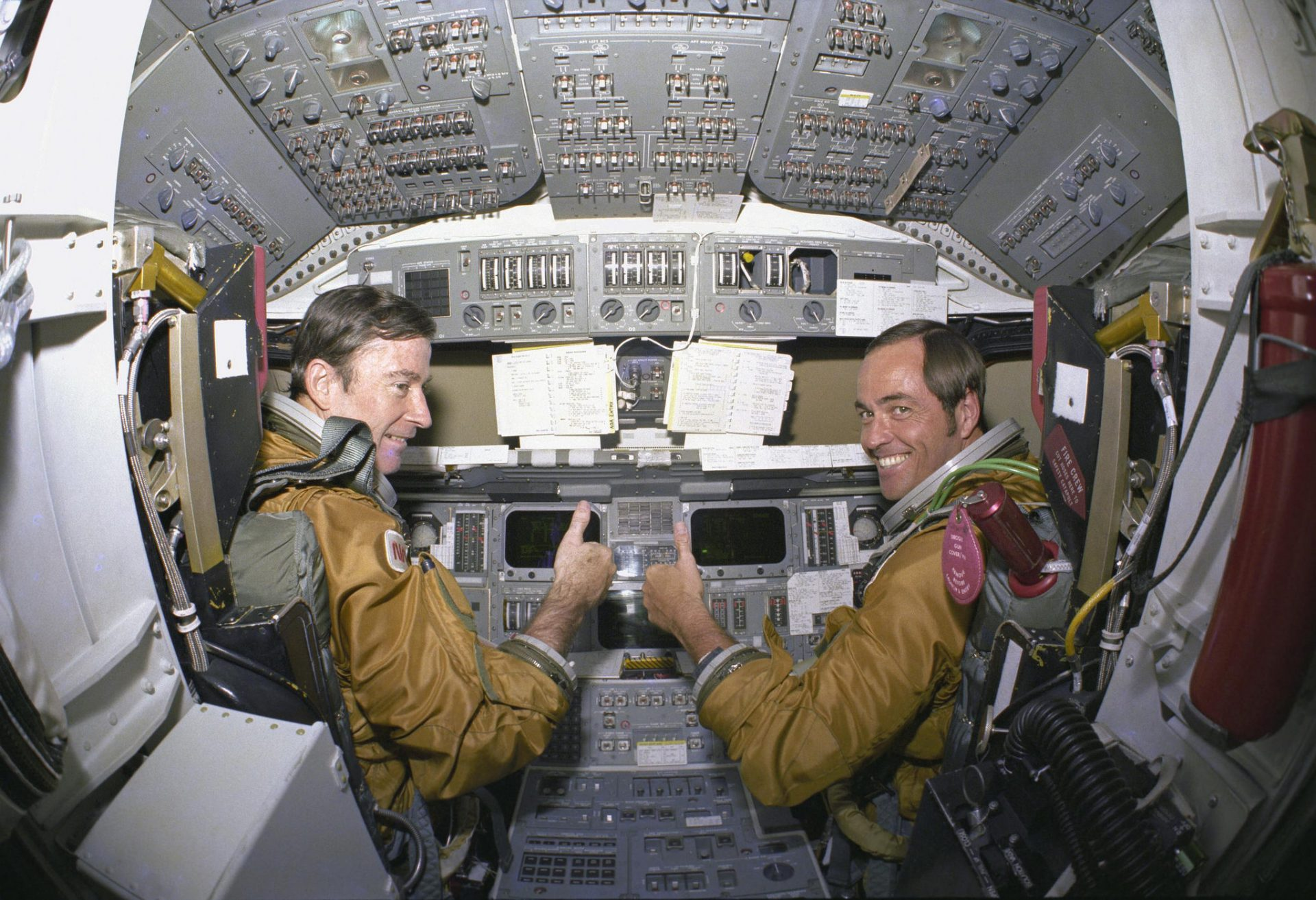 Commander John Young and Pilot Robert Crippen, take a break from their intensive training schedule to pose for pictures in the flight deck of the shuttle Columbia.