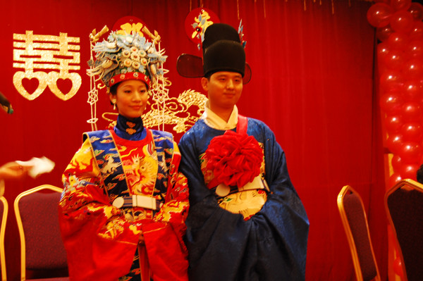 Traditional Chinese wedding ceremony, with a double happiness character in the background. (Image: Hanfu Love via flickr CC BY 2.0 )