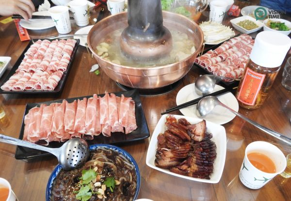 Hot pot usually consists of a simmering metal pot with broth in the middle of a dining table, and all raw ingredients are placed around the metal pot. (Image: Julia Fu / Vision Times)