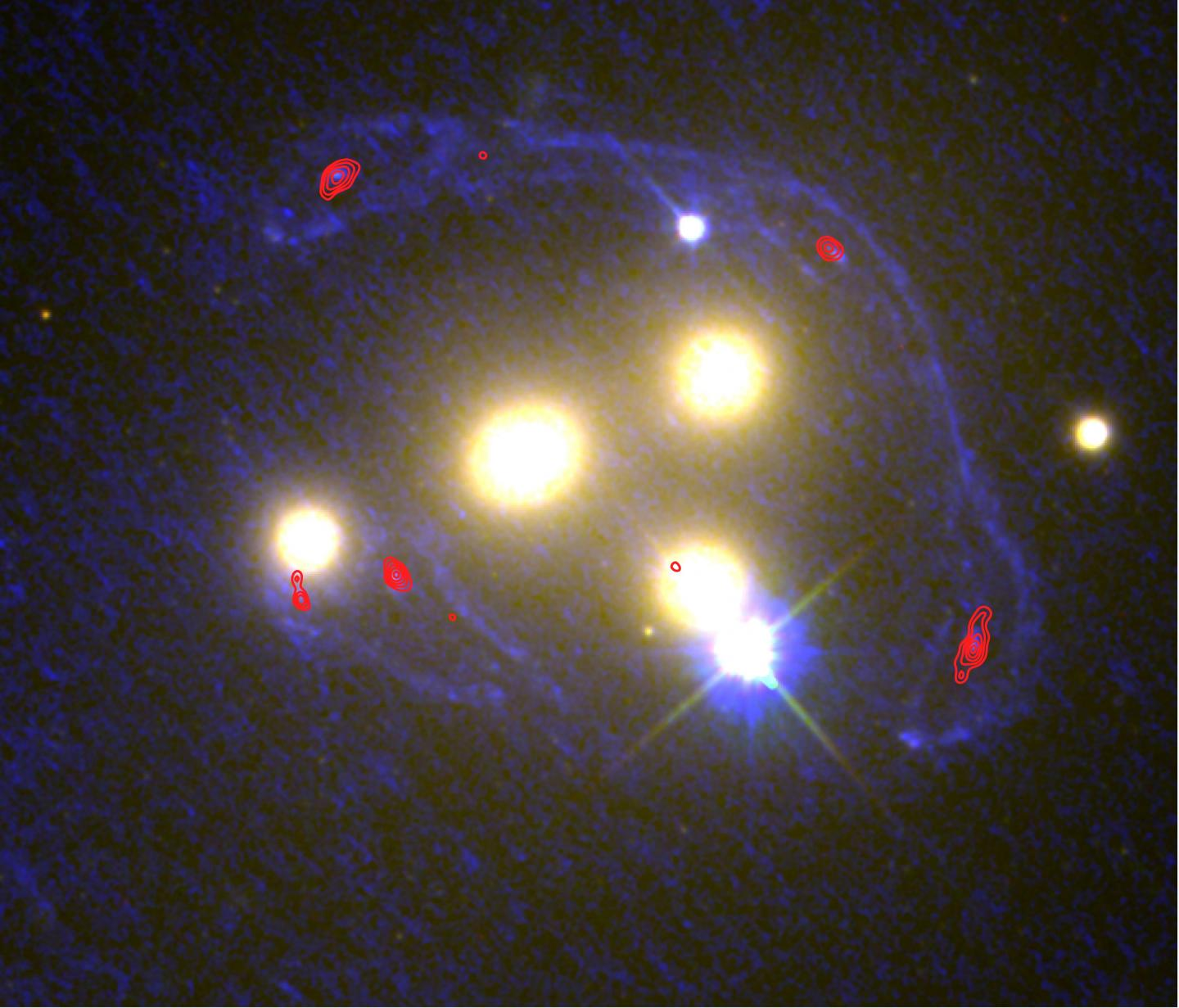 A view of the four central galaxies at the heart of cluster Abell 3827, at a broader range of wavelengths, including Hubble Space Telescope imaging in the ultraviolet (shown as blue), and Atacama Large Millimetre Array imaging at very long (sub-mm) wavelengths (shown as red contour lines). At these wavelengths, the foreground cluster becomes nearly transparent, enabling the background galaxy to be more clearly seen. It is now easier to identify how that background galaxy has been distorted. (Image: NASA/ESA/Richard Massey (Durham University)