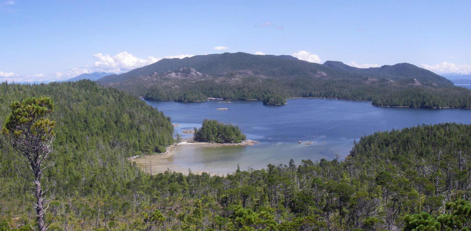 View across the beach at EjTa-4 with Calvert Island in the foreground and Hecate Island in the background. Photo by Jim Stafford.