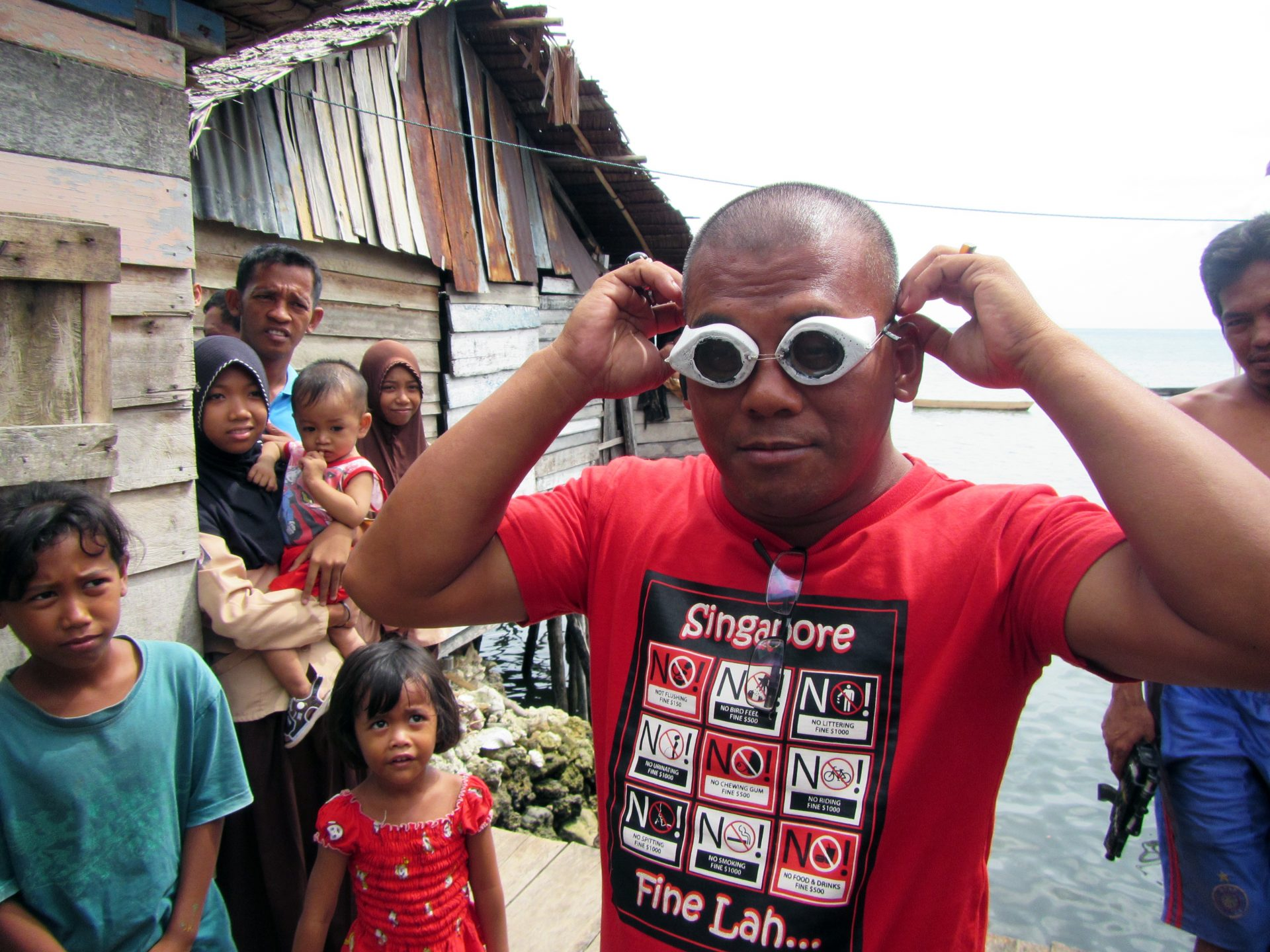 A Bajau villager demonstrates the use of traditional wooden goggles. (Photo by Melissa Ilardo)