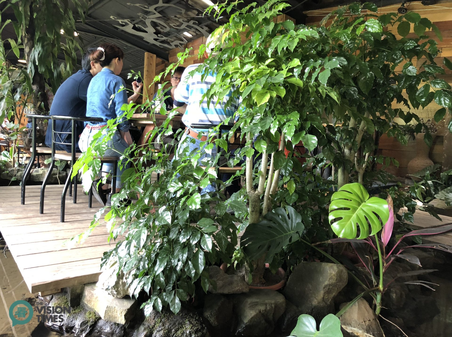Visitors can dine around a wooden table next to green plants on elevated solid wood floor made of planks. (Image: Billy Shyu / Vision Times)