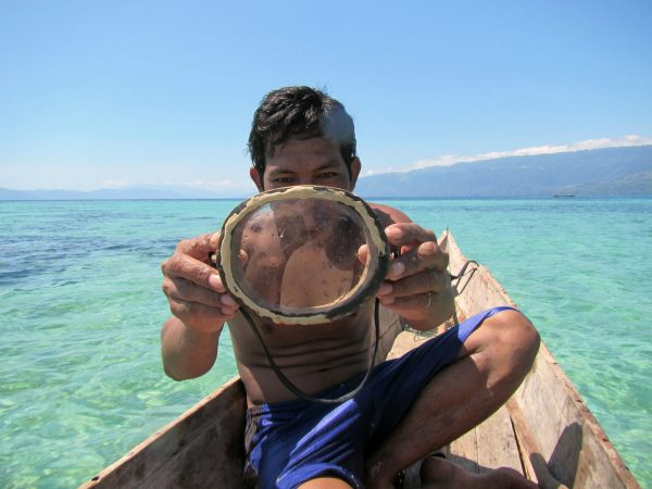 A Bajau diver displays a traditional wooden diving mask. (Photo by Melissa Ilardo)