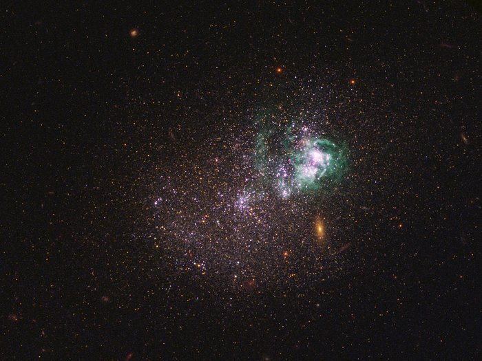 UGCA 281 is a blue compact dwarf galaxy located in the constellation of Canes Venatici. Within it, two giant star clusters appear brilliant white and are swaddled by greenish hydrogen gas clouds. These clusters are responsible for most of the recent star formation in UGCA 281; the rest of the galaxy is comprised of older stars and appears redder in colour. The reddish objects in the background are background galaxies that appear through the diffuse dwarf galaxy. The image is a composite using both ultraviolet light and visible light, gathered with Hubble's Wide Field Camera 3 and Advanced Camera for Surveys. (Image: NASA, ESA, and the LEGUS team)