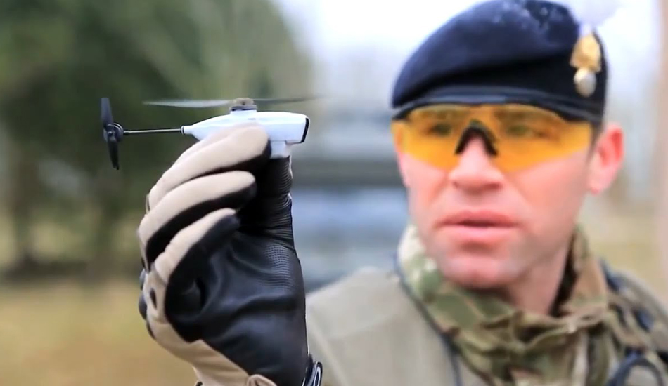 An army soldier holding a small military-grade drone.