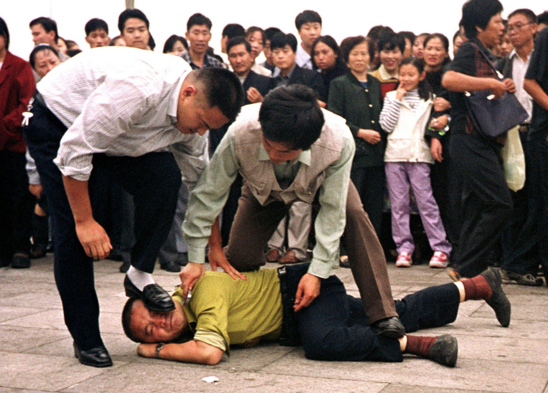 The photo shows Chinese plainclothes police in Tiananmen Square stamping on the face of a man for protesting the communist regime's persecution of the Falun Gong spiritual practice. (Image: Minghui.org)