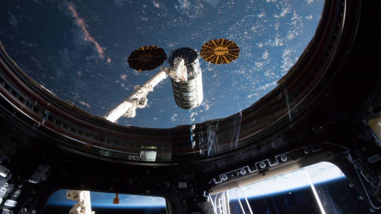 Taken from inside the Cupola on the International Space Station, this image shows the Northrop Grumman (formerly Orbital ATK) Cygnus spacecraft arriving at the station on May 24, 2018. The vehicle carried, among other things, NASA's Cold Atom Laboratory. (Credits: NASA)