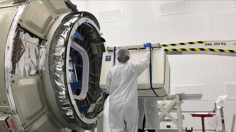 The Cold Atom Laboratory (CAL), packaged in a protective layer, is loaded onto a Northrop Grumman (formerly Orbital ATK) Cygnus spacecraft for its trip to the International Space Station. The facility launched in May 2018 from NASA's Wallops Flight Facility in Virginia. (Credits: NASA/Northrop Grumman)