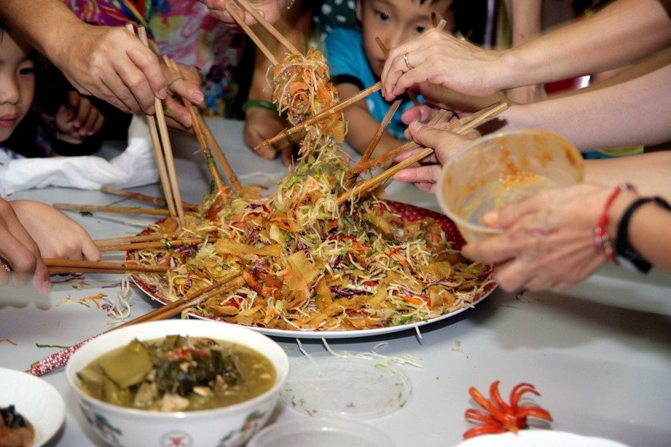 Hand with chopsticks grabbing fried noodles from a plate and a chinese boy in the background