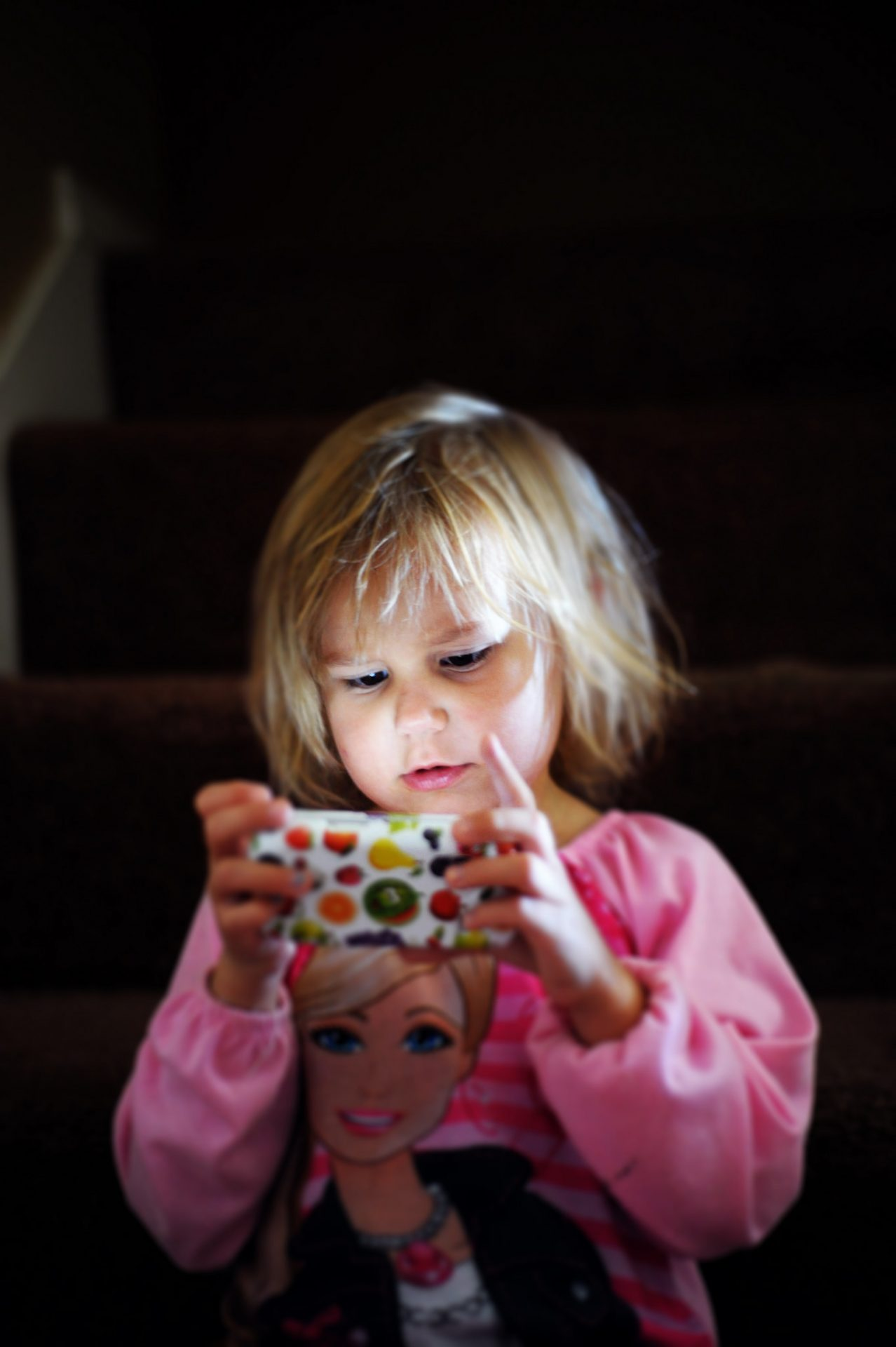 little girl dressed in pink holding a smartphone in hand, starring at the screen. Lights to t