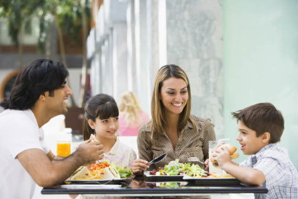 Family sits at a table in public, father with dark hair followed by a daughter, mother and a son.