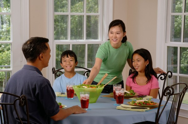 Asian Family at the table. Father two children and a mother reaching from inbetween the children passing the father a green salad bowl.