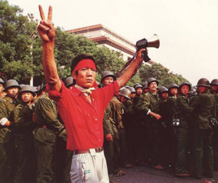 A student pro-democracy protester flashes victory signs to the crowd on June 3, as troops withdraw on the west side of the Great Hall of the People near Tiananmen Square. (Image: Public Domain)