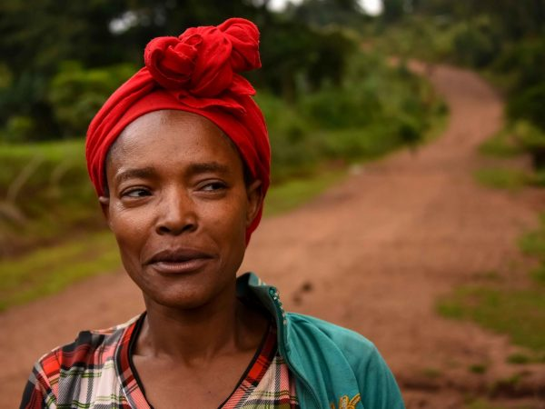 Ethopian woman with red head dress, posing for photo
