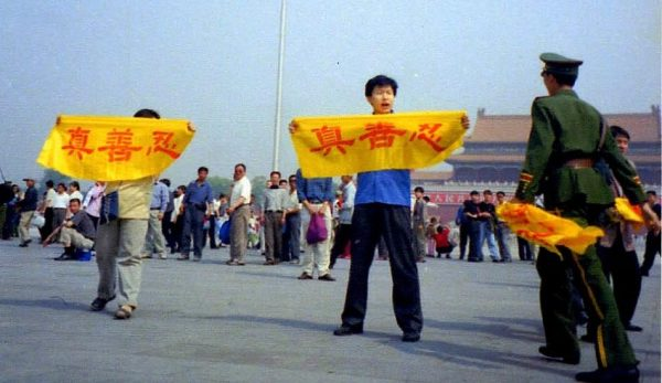 "A Falun Gong practitioner holds a banner at Tiananmen Square reading ""Truth, Compassion, Tolerance,"" the core tenets of the practice. A policeman approaches to arrest him. (Image: Falun Dafa Information Center)"