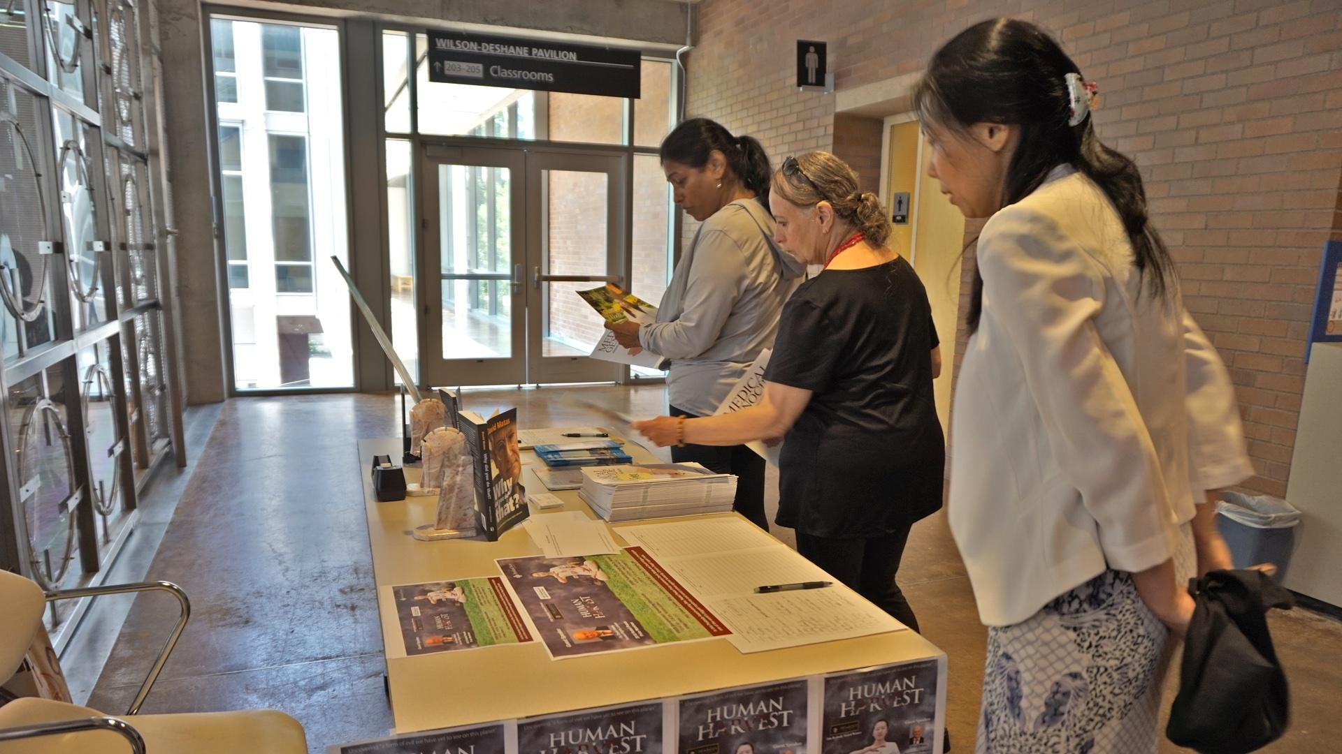 People look at materials raising awareness about forced organ harvesting in China following the screening. (Image: Vision Times)
