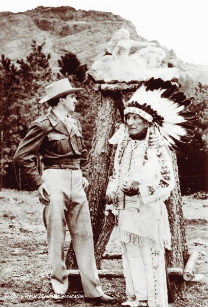 Korczak Ziolkowski and Chief Standing Bear in front of a scale model of the Crazy Horse Memorial. The mountain in the distance would become the site of the memorial. (Image: Crazy Horse Memorial Foundation)