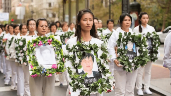 Family members march holding images of loved ones killed by the CCP. (Image: Screenshot / YouTube)