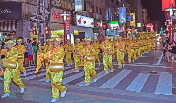 The Falun Dafa Waist Drum Team's majestic performance wins warm applause along the procession route. (Image: Johnny Lin / Vision Times)