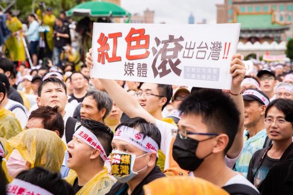 """A protester holds up a sign with the words """"Red Media Get Out of Taiwan"""" in Chinese in a rally in Taipei, Taiwan, on June 23, 2019. (Image: Chen Pochou/The Epoch Times)"""