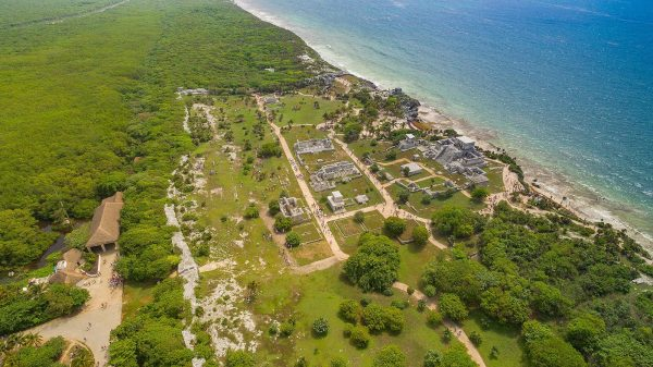 Ruins of tulum, ocean water, sand beach and green pastures