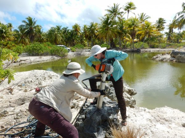 Pam Grothe and Alyssa Atwood drill into a 5,000-year-old coral fossil on Kiritimati Island. (Image: Georgia Tech / Grothe / Cobb lab)