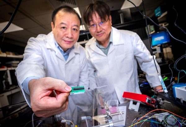 (L-R) NTU Prof Liu Ai Qun and Assoc Prof Kwek Leong Chuan showing the tiny 3mm quantum communication chip embedded on the bottom right of the green circuit board, which is 1,000 times smaller than current setups and provides almost unhackable levels of encryption. (Image: NTU Singapore)