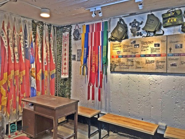 """There are various army flags, a counterfeit carbine, a gas mask, and other military gear displayed at """"Checkpoint 23""""in Matsu's Juguang Island. (Image: Billy Shyu / Vision Times)"""