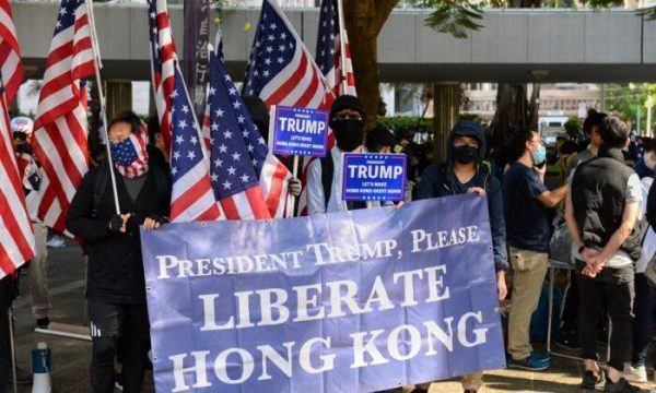Protesters hold up a banner and U.S. flags at a rally at Charter Garden in Hong Kong. (Image: Sun Pi-lung/The Epoch Times)